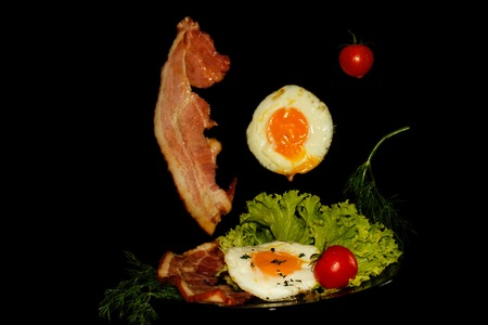 Full English breakfast with scrambled eggs in a frying pan, bacon, sausage, beans, tomatoes. Black background