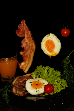 Full English breakfast with scrambled eggs in a frying pan, bacon, sausage, beans, tomatoes and juice. Black background