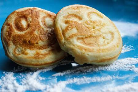 pancakes with a smile on a blue background. Stock Photo