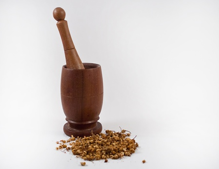 Mortar and pestle with dried herbs on a white background.