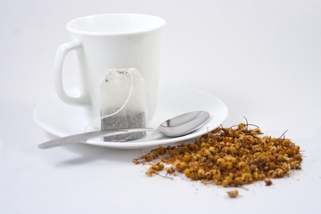 White tea cup, tea bag and loose herbal tea on white background. photo