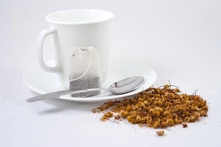 White tea cup, tea bag and loose herbal tea on white background. Stock Photo - 10506778
