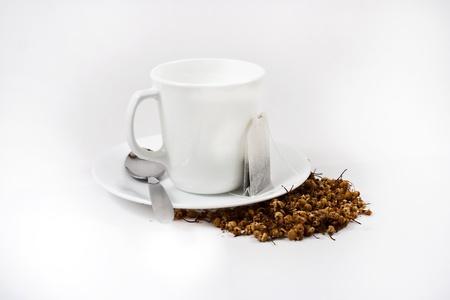 White tea cup, tea bag and loose herbal tea on white background. photo