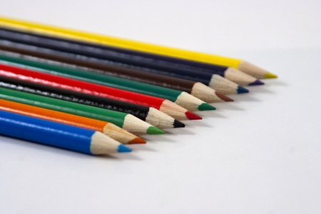 Color pencils evenly laid on white background.