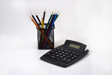 Color pencils in black pencil holder and calculator on white background. photo