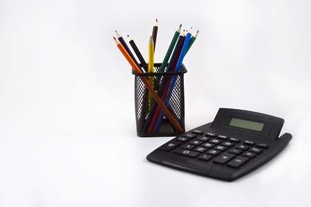 Color pencils in black pencil holder and calculator on white background. Stock Photo - 10506774