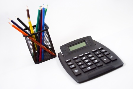 Color pencils in black pencil holder and calculator on white background. Stock Photo - 10506780