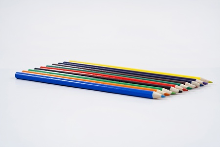 Color pencils evenly laid on white background. photo