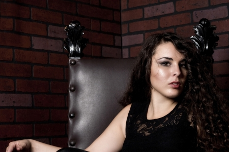 A sexy model seated in an antique leather chair with a brick background. Stock Photo
