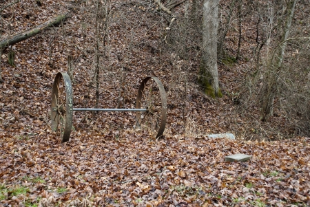 An old wagon wheel axle and wheels left abandoned in woods.