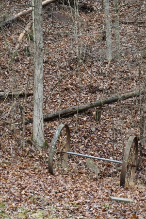 An old wagon wheel axle and wheels left abandoned in woods. Stock Photo - 17097565
