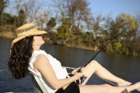 A mature woman enjoys the day while fishing on a boat.
