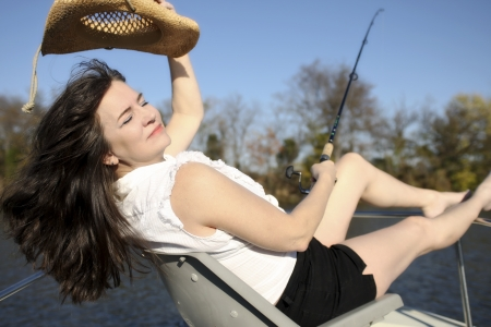 A mature woman enjoys the day while fishing on a boat. photo