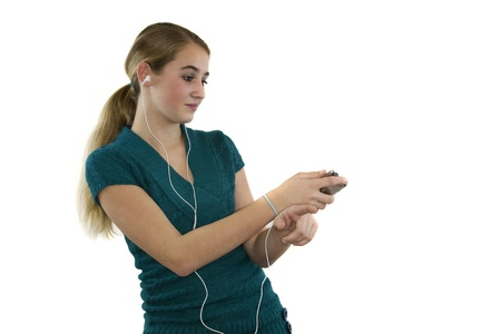 Young female listens to music with ear plugs while dancing on white background isolated.
