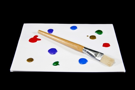 A paint brush and colorful paints create a painters palette. Stock Photo