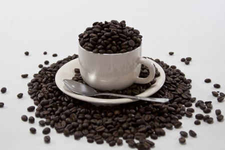 Coffee Beans Overflow Coffee Cup on Isolated White Background photo