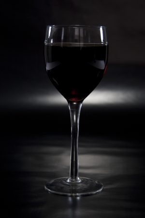 Glass of Wine Spotlighted on Reflective Black Background photo