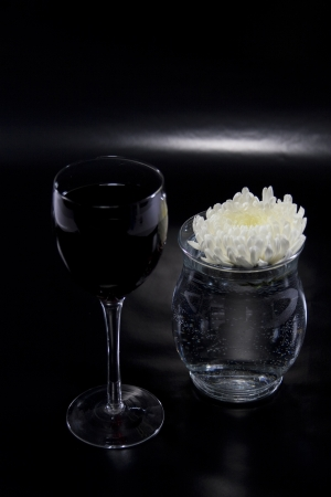 Glass of Wine and Flower Spotlighted on Reflective Black Background Stock Photo