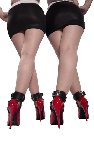 Two sets of red heels, legs and cuffed ankles  Stock Photo