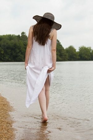 An attractive female strolls along the waters edge. Stock Photo