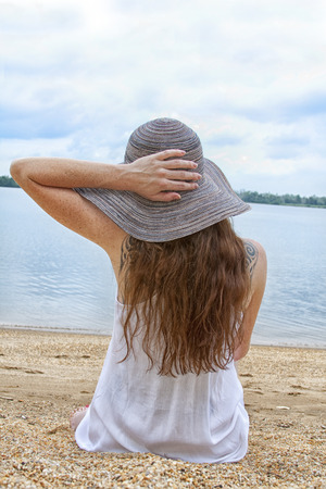 A female in a beach hat gazes out at the lake on a Summer day. Stock Photo