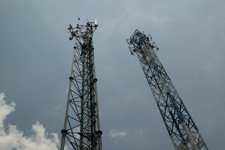 two telecommunications towers against the sky photo