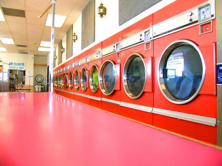 Row of commercial clothes dryers, in retro orange color Stock Photo