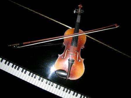 atop:           classic stradivarius violin atop a  grand piano