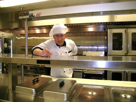 dinner wear:            Chef on Commercial Industrial Kitchen Line, Bright and Shiny Stock Photo
