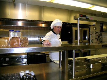 Chef on Commercial Industrial Kitchen Line, Bright and Shiny Stock Photo