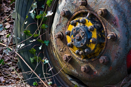 A tractor has been rusting for years on the yard of a farm. Most of it has disappeared, but the wheel and an axle are still there