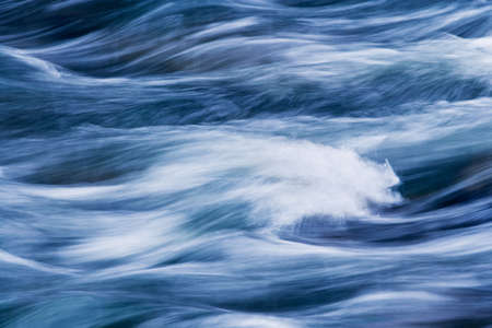 appearing: Water rushing by in a river forming a smooth, abstract, painted appearing pattern. Stock Photo