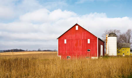 barn wood: A red barn in a field with a cloud filled blue sky.