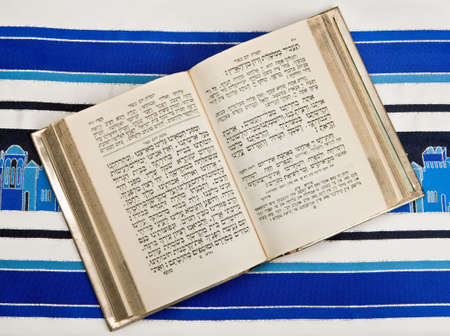A Jewish prayer book, or Siddur, open and on top of a prayer shawl or Tallit. photo