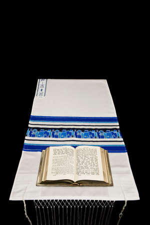 A Jewish prayer book, or Siddur, on a prayer shawl, or tallit, against a black background. Stock Photo - 3851881