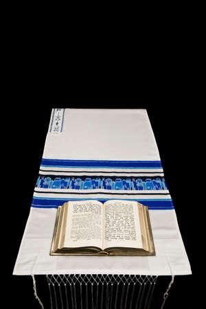 tallit: A Jewish prayer book, or Siddur, on a prayer shawl, or tallit, against a black background.
