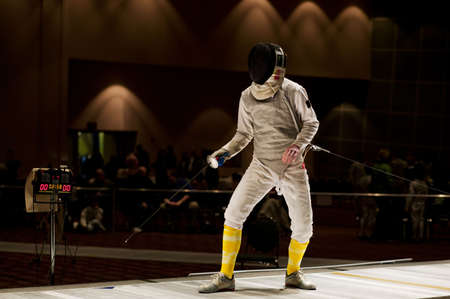 bout: A competitive foil fencer stands ready to begin a fencing bout at a tournament.