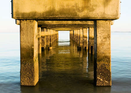 A view with an unusual perspective from underneath the concrete base of a wharf looking out onto the Gulf Of Mexico. photo