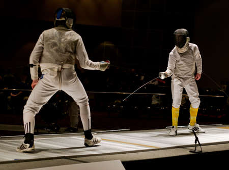 begin: Two foil fencers approach each other in a championship bout and begin to fence.