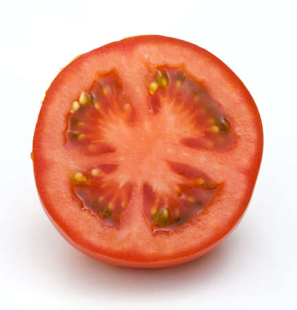 slice tomato: A juicy, delicious, cut tomato half on a white background which conveys the idea of a healthy diet.