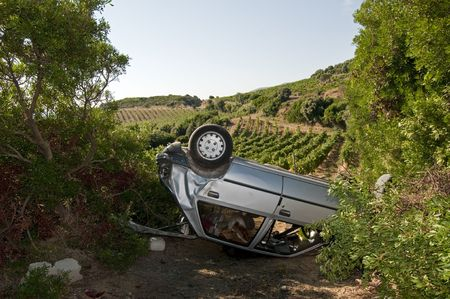 Crashed car overturned in a field photo
