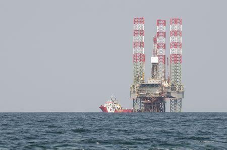 boat lift: Oil rig on the sea with red and white cargo ship