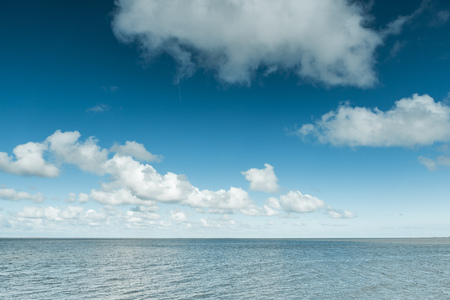landschaft: Nautical background of a calm blue ocean on the North Sea Coast, Germany on a sunny day with fluffy white clouds in a blue sky in a panoramic view