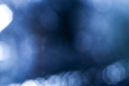 Dark overlay background of blue LED lights with bokeh effect. Includes copy space.