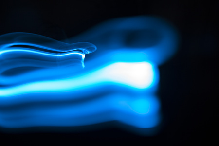 Blue and white streaks of light over black background with copy space for concept about natural gas Stock Photo