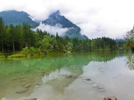 Mountain peaks shrouded in cloud and mist surrounded by evergreen forests in Austria