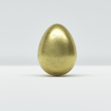 One golden Easter egg on grey background in close-up, balanced vertically on its blunt end