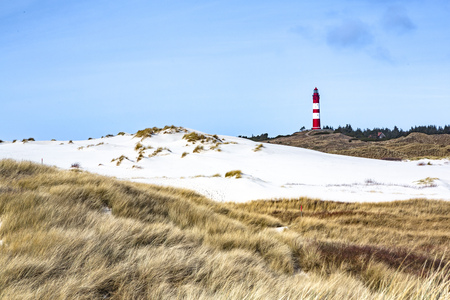 Red and white lighthouse on the hill viewed from low angle with dry grass and white sand dunes trail in foreground on a sunny day in Amrum, Germany, Schleswig-Holstein Stockfoto