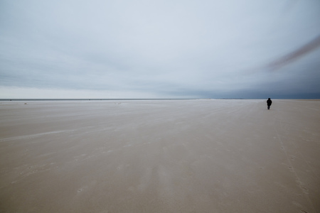 Person in the middle of wide sandy beach landscape against overcast sky on moody day at North Sea, Amrum, Norddorf, Germany, Schleswig-Holstein