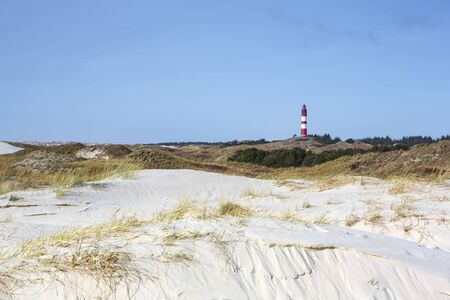Red and white lighthouse on the hill viewed from low angle with dry grass and white sand dunes trail in foreground on a sunny day in Amrum, Germany, Schleswig-Holstein Stock Photo